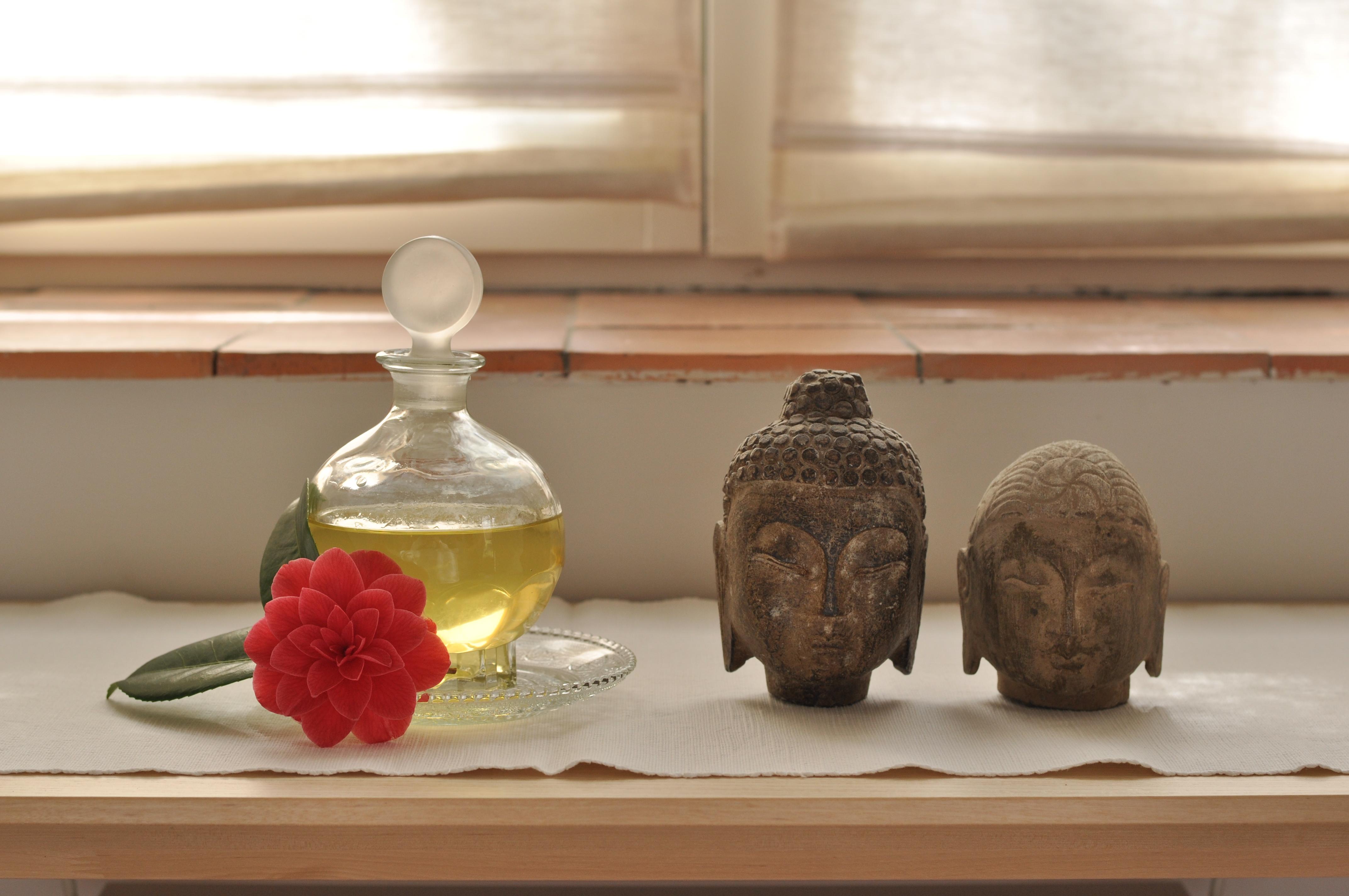 huile naturelle avec une fleur de camélia et 2 têtes de bouddha