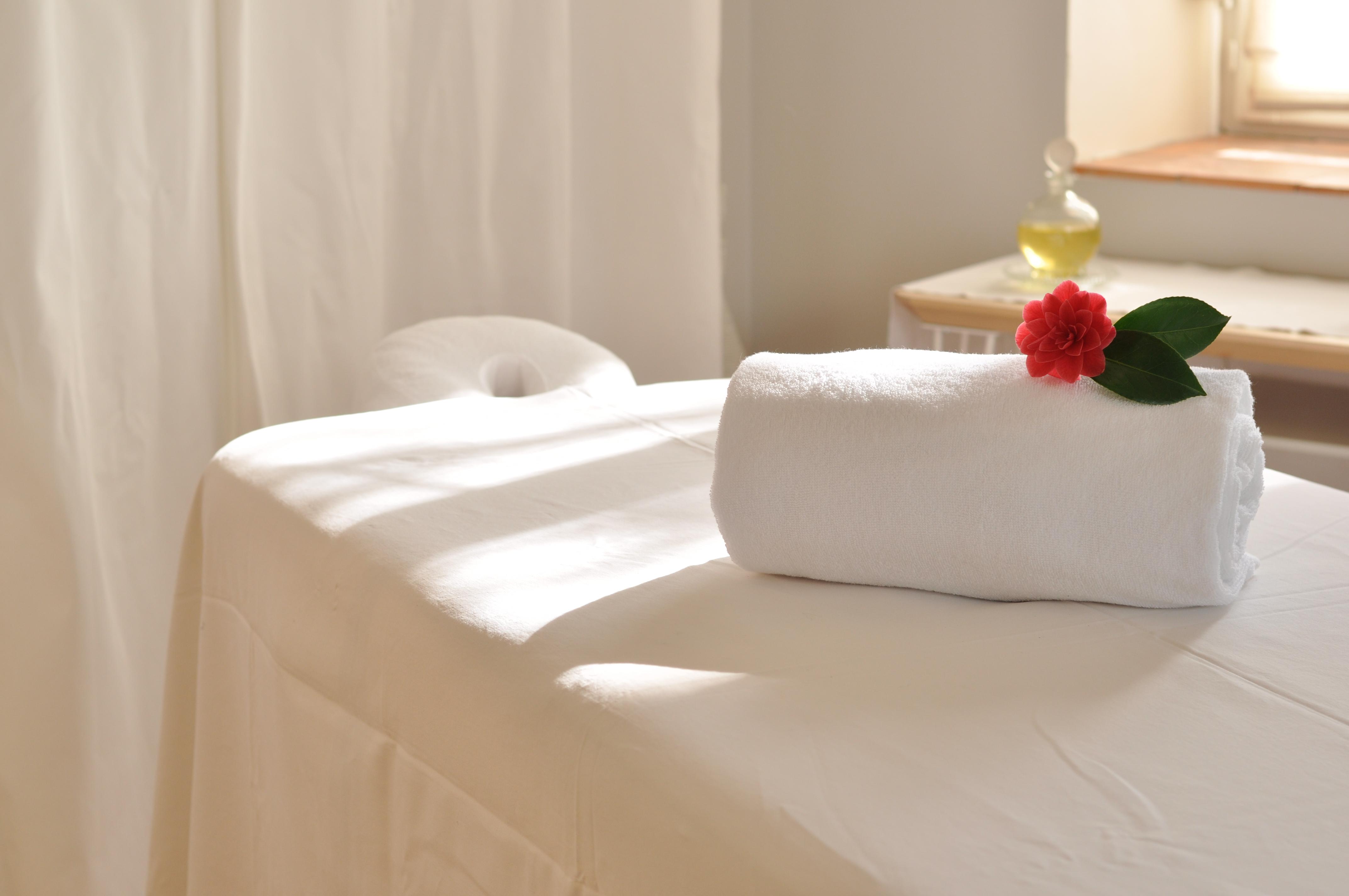 Table de massage et têtière, serviette de toilette roulée, fleur de camélia, flacon d'huile, rideaux blancs nioumii massage & beauté Marcq en Baroeul